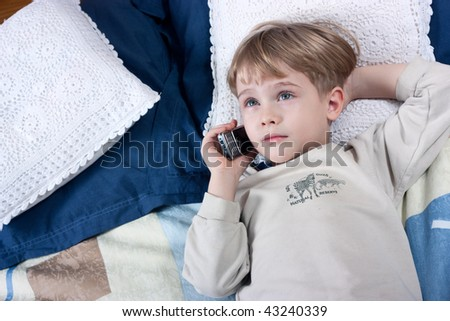 Little boy talking by mobile phone very emotional
