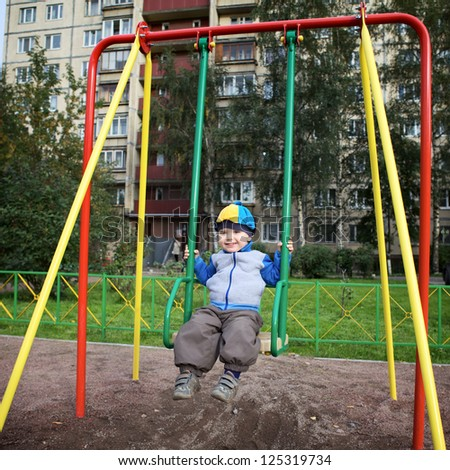 little boy teeter on playground at autumn