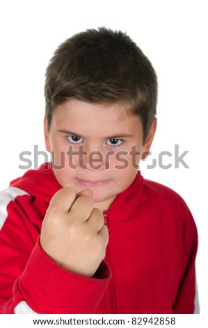Little boy threatens with a fist on a white background
