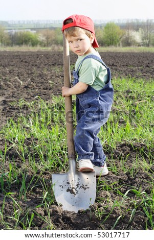 Little boy to dig on field with big shovel, looking to camera