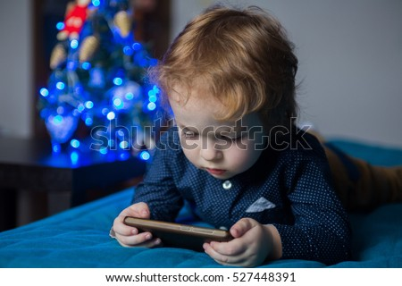 little boy toddler lying  on the couch and watching plays in the  smartphone #527448391