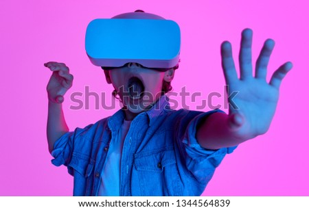 Little boy touching air with hands and screaming with amazement while using VR goggles on pink backdrop. Teenager playing a game in virtual reality world