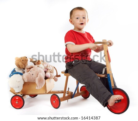 Little boy transporting his teddy bears and dolls in a cart