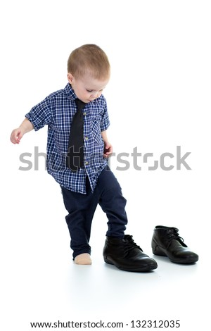 little boy trying on father shoes