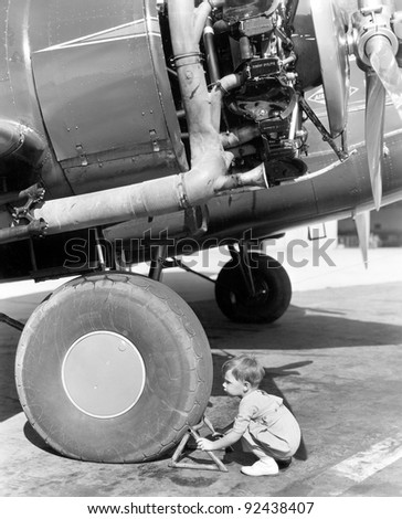Little boy trying to fix an airplane wheel