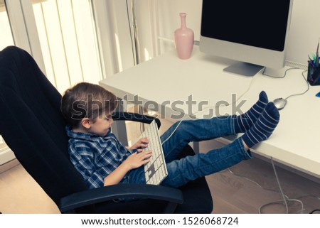 Little boy typing on computer keyboard while surfing the net on desktop PC. #1526068724