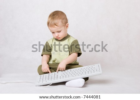 little boy typing on keyboard