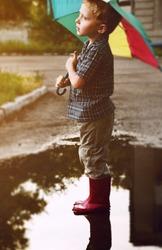 Little boy under bright umbrella after summer rain