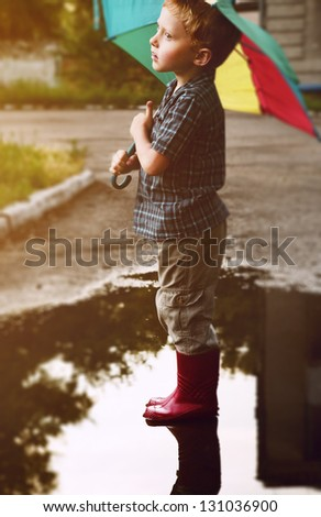 Little boy under bright umbrella after summer rain