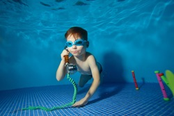 Little boy underwater swims and plays in the pool with the handset. Portrait. Shooting underwater. Landscape orientation