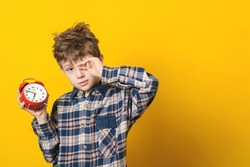 Little boy waking up with alarm clock, isolated on the yellow background.