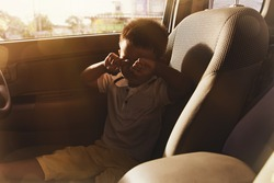 Little boy was alone in the car, crying, shocked and worried by the lack of care from his parents who left alone in the seat of the car : Neglect leading to accidents and negligence concept