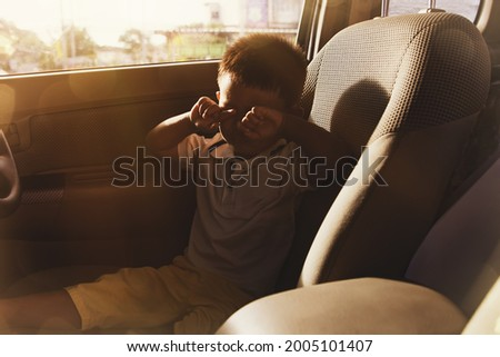 Little boy was alone in the car, crying, shocked and worried by the lack of care from his parents who left alone in the seat of the car : Neglect leading to accidents and negligence concept Stock photo ©