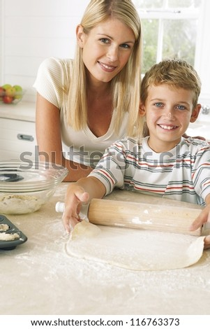Little boy watched over by his mother learning to bake as he rolls out the dough with the rolling pin