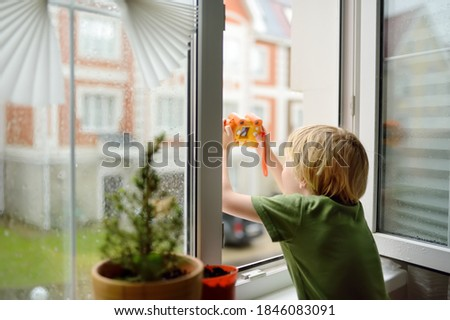 Photo of  Little boy watching the rain outside at opened window and taking photo. Bad weather - wind and downpour. Child boring and waiting of rainfall finish. Inquisitive kid explore nature.