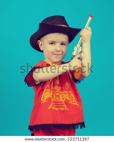 a488770baa206 little boy wearing a cowboy hat a over blue background  523711387