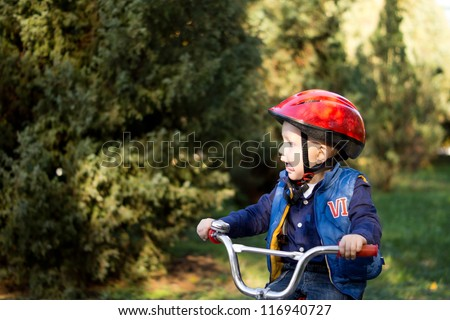 Little boy wearing a red crash helmet riding a bicycle outdoors on his own with copyspace