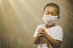Little boy wearing mask for protect pm2.5 and Covid-19. He praying in the morning for a new day freedom to wuhan corona virus. Asian boy hand praying for thank GOD. Copy space.