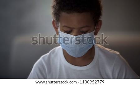 Little boy wearing protective medical mask, illness prevention, ebola epidemy