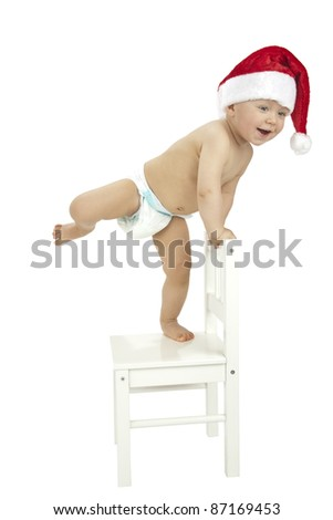 Little boy wearing Santa hat (standing on chair with leg up) - stock photo