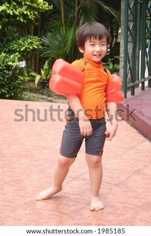 Little boy wearing swimming costume, standing bare-footed