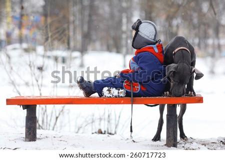 little boy with a big black dog breed