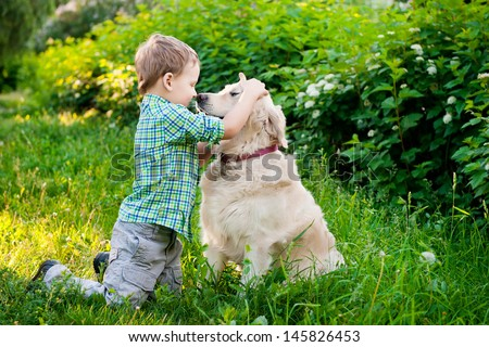Little boy with a golden retriever - stock photo