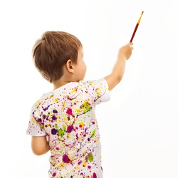 Little boy with a paintbrush, rear view, isolated on white background