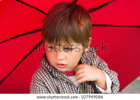 Little boy with a red umbrella in his hand is listening to the rain. His face collected.