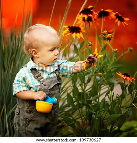 little boy with a watering can check the quality of flowers