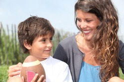 little boy with American football sat with mother