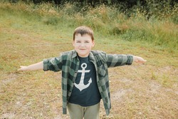 Little boy with an anchor on his t-shirt smiles happily and keeps arms wide open. Boy by the sea. Little child flies with his hands