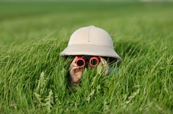 Little Boy with Binoculars and safari Hat, laying in the grass searching for Knowledge