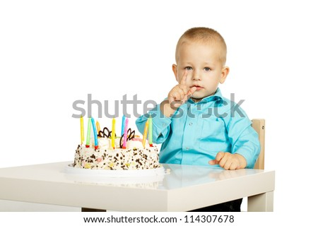 little boy with birthday cake shows two years with fingers
