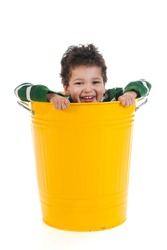 Little boy with black curly hair in yellow trash can isolated over white background