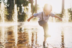 little boy with blond hair walking around the city and enjoying the sunshine