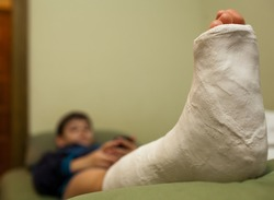 Little boy with broken leg in plaster cast lying on sofa at home and using smart phone. Focus in foreground