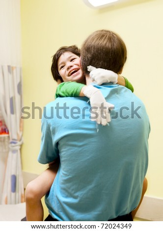 Little boy with cerebral palsy in doctor's office, laughing with his father