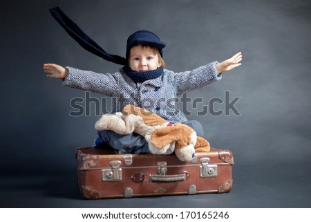 Little boy with coat and hat, sitting on a suitcase with his teddy dog friend