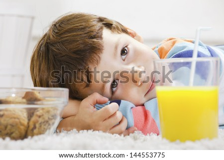 Little boy with cookies and orange juice stretching on carpet./ Closeup of child with breakfast in home.
