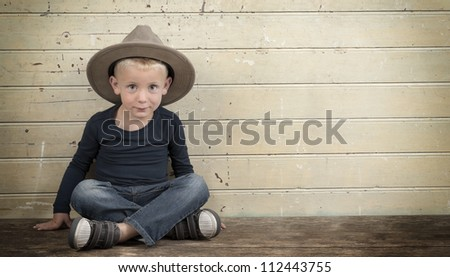 little boy with cowboy hat seated against an old wooden door