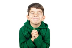 Little boy with cute face folds his hands in front of him and praying on a white background, isolated. Boy asks God for Christmas presents for poor children. Place for text