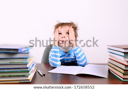 little boy with disheveled hair  sitting at a desk and looking up. boy 5 years. on the desk a lot of books. photo taken on a light background