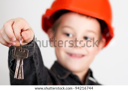 little boy with drawing and in hard hat.