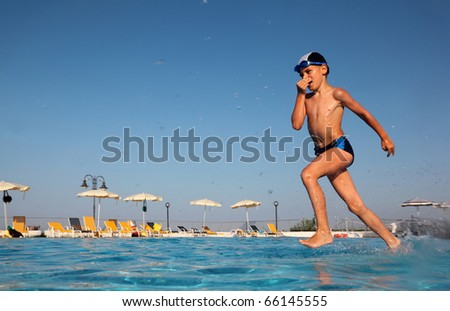 little boy with glasses for swimming dives into blue, clear water of pool. in background beach umbrellas. from the underwater package