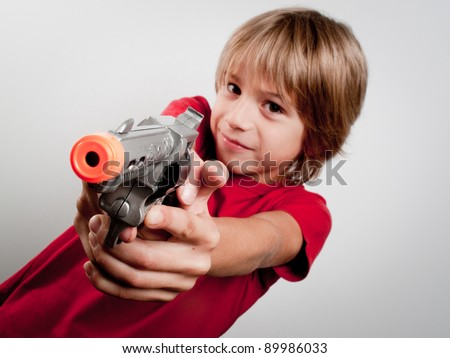 little boy with gun toy