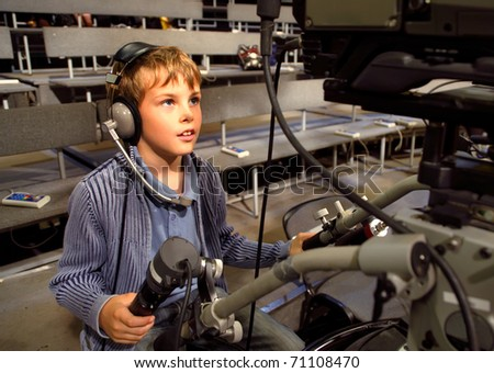 Little boy with headphones and microphone sits on the professional video camera in auditorium on television broadcast
