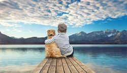 little boy with his dog on the pier - autumn on the mountain lake