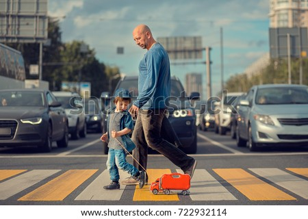 Little boy with his father and a red toy track are crossing the street on crosswalk. A lot of cars are waiting them. Image with selective focus and toning