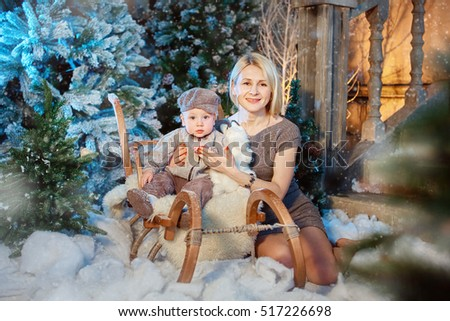 Little boy with his mother enjoying sledding. Toddler baby rides in a sleigh. Outdoor fun for the family Christmas vacation. Fir and snow. Photo session in the interior